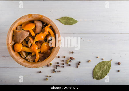 pickled mushrooms in wooden utensils on a white background - Stock Photo