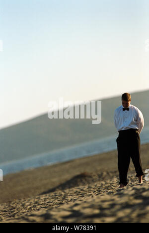 Lonely groomsman standing in bare feet on a sandy beach. - Stock Photo