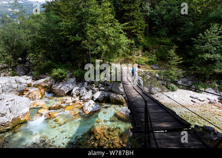 Young boy crossing a wooden suspension bridge over beautiful turquoise Soca river while trekking on Soca trail, Bovec, Slovenia, Europe - Stock Photo