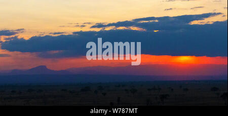 Viewed from Mikumi National Park from the Stanley's Koppie Lodge on a clear afternoon the sun sets showing the relief of the Udzungwa Mountains. - Stock Photo
