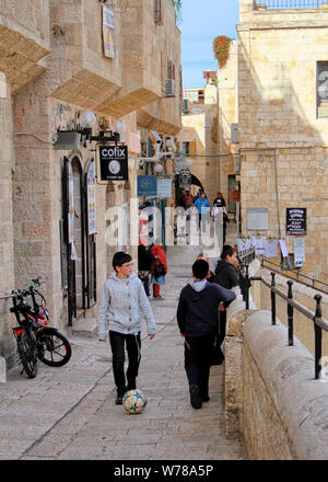 Boys kick a soccer ball down a street in the Jewish Quarter of Jerusalem's Old City, near the Roman Cardo. - Stock Photo
