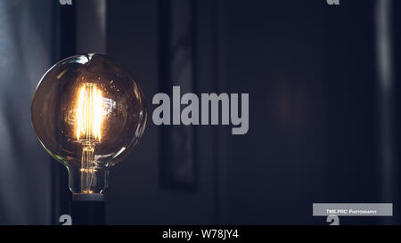 Glowing yellow light bulb, Realistic photo image turn on tungsten light bulb. Energy and idea symbol. Decoration for greeting cards, patches, prints f - Stock Photo