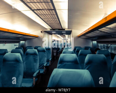 Image with the interior of a china border train. A modern train with comfortable and colorful chairs - Stock Photo