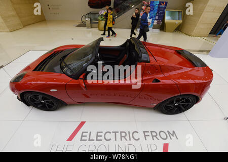 Customers look at a Tesla Roadster, a battery electric vehicle (BEV) sports car of Tesla, on display at a shopping mall in Hangzhou city, east China's - Stock Photo
