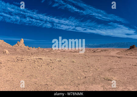 Brown hot dry barren desert valley with Pinnacles under bright blue sky sky with white clouds. - Stock Photo