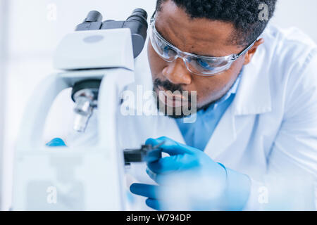 Man does scientific research with the microscope in the lab.