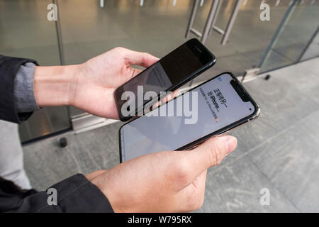 A Chinese customer is making an registration on his new iPhone X smartphone, right, in front of an Apple store in Shanghai, China, 3 November 2017. - Stock Photo