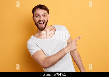 positive guy with wide open mouth indicates at copy space. hurry up, sale. close up portrait. isolated blue background. studio shot. emotion and feeli - Stock Photo