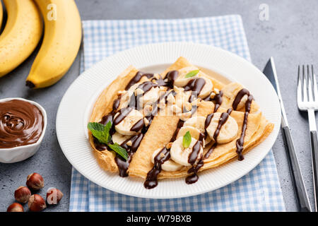 Tasty crepe with banana and chocolate sauce on white plate. French thin pancakes or russian blini for dessert - Stock Photo