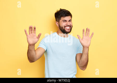 angry frustrated man showing his palms, isolated yellow background, studio shot, guy retracting a claim - Stock Photo
