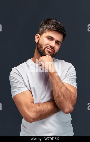strong muscular thoughtful serious confident guy holding his hand under chin, close up portrait, studio shot, let me think - Stock Photo