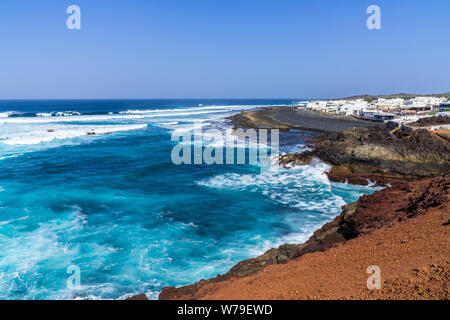 Spain, Lanzarote, Rough west coast waves at little fishing village of el golfo - Stock Photo