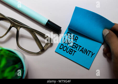 Fear Uncertainty Doubt (FUD) text on sticky notes isolated on office desk - Stock Photo