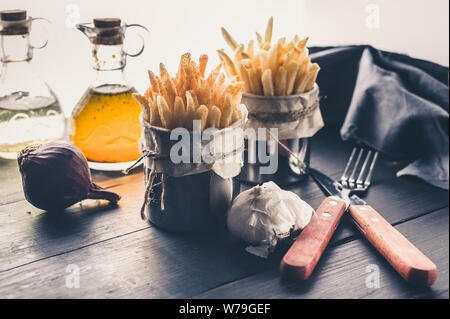 French fries in the iron banks, olive oil, onion and garlic on a dark wooden table. Low key - Stock Photo