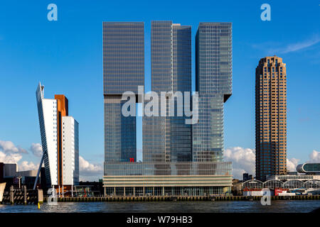Cityscape with modern skyscraper buildings in the financial district and port area of the Dutch city against a clear blue sky - Stock Photo