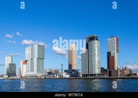 Cityscape of Rotterdam financial district with high rise modern buildings in the port area of the Dutch city against a blue sky and clouds - Stock Photo