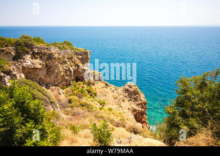 Beautiful view from the cliff of the sea. The water is clear with a blue tint. Bushes and various vegetation grow on the rock. - Stock Photo