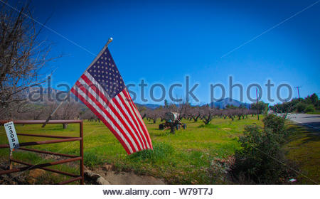 Ojai, United States - February 25 , 2013 : A winding road in ojai, proud of being american, stars and stripes flag hanging out in front.