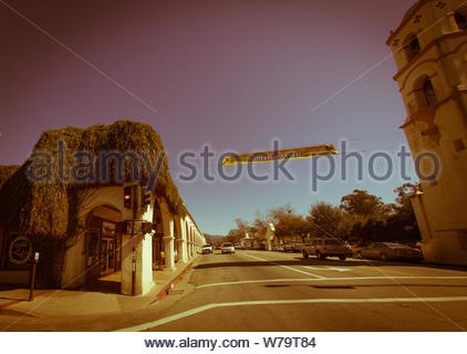 Ojai, United States - February 25 , 2013 : A shop on the main street down town has been overgrown by ivy, wild plants and hills in the background. - Stock Photo