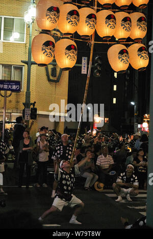 Crowds watch as a man balances a bamboo pole full of traditional candlelit Japanese lanterns on his shoulder at Akita Kanto Matsuri Festival in 2016. - Stock Photo