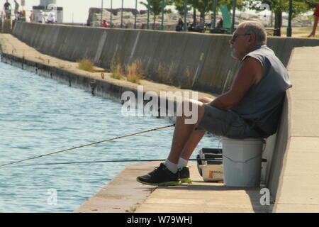 Older man sitting on a bucket fishing on Lake Michigan in Kenosha, Wisconsin on a hot summer morning in August, 2019. - Stock Photo