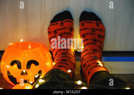 kids legs in stylish warm bright colorful striped funny socks in garland lights on floor with pumpkins in room. decor for Halloween, cosy moment. - Stock Photo