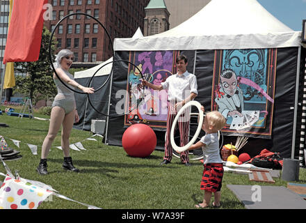 Neo-vaudevlile performers play with a blonde-haired boy outside their performance tent on Public Square in downtown Cleveland, Ohio, USA. - Stock Photo