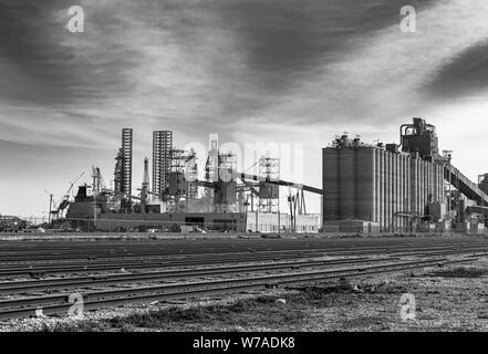 ADM grain facility In Galveston Texas, right along the Galveston Channel with numerous railroad cars. - Stock Photo
