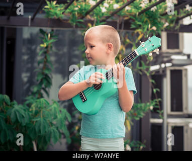 Portrait of a cute boy sitting ouddoor with ukulele - Stock Photo