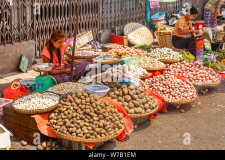 Yangon, Myanmar - May 4th 2014: Women selling vegetables on a street market. Street markets can be found everywhere. - Stock Photo