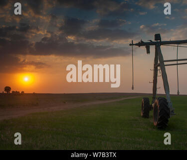 The self-propelled irrigation system in fields on the border of Israel, Egypt and the Gaza Strip photographed on sunset - Stock Photo