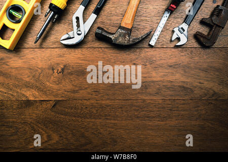 Grungy rusty craftsmen Tools like water scale, pliers, screwdriver, Hammer and tape measure on wooden planks with room for writing - Stock Photo