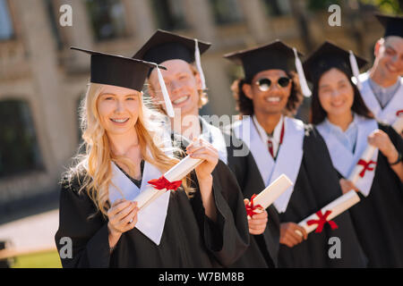 Blond girl standing in front of her groupmates. - Stock Photo