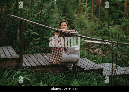 Resting smiling girl in a simple plaid shirt sits on a wooden ladder in a pine green forest - Stock Photo
