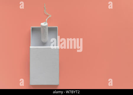 Menstrual period concept. Woman hygiene protection. Cotton tampon  in a white boxon on coral background. Copy space and mockup; - Stock Photo