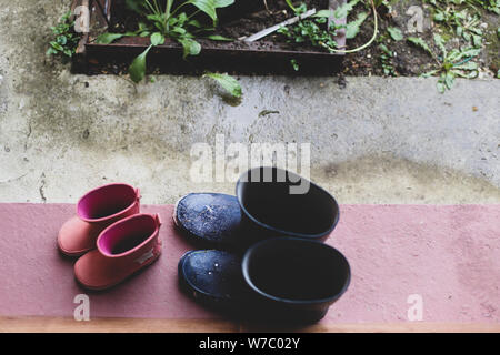 Two rubber boots pairs (father and daughter) on the porch at the entrance of the house during a rainy day - Stock Photo