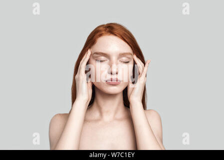 Studio shot of beautiful redhead woman keeping eyes closed and touching head with hands while standing against grey background - Stock Photo