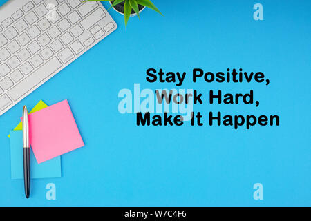 Flat lay, top view office table desk. Workspace with STAY POSITIVE WORK HARD MAKE IT HAPPEN inscription written with keyboard, pen and sticky notes on - Stock Photo