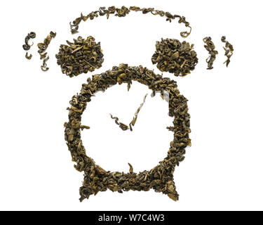 Ringing alarm clock shape made of dry Oolong tea leaves isolated on white background. Fermented Chinese green tea. - Stock Photo