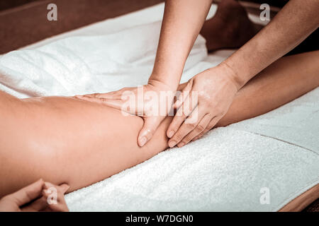 Masseuse doing oil massage of clients hips. - Stock Photo