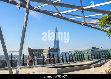 A male tourist looking over cityscape from The Garden at 120, a roof garden in the city of London - Stock Photo