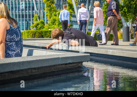 London, UK - July 16, 2019 - A tourist finding angles to take pictures from his smartphone on The Garden at 120, a roof garden in the city of London - Stock Photo