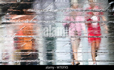 Blurry reflection shadow silhouettes of  people walking on a rainy pedestrian city wet street  on a summer day, in a puddle - Stock Photo