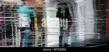 Blurry reflection shadow silhouettes of  people walking under umbrella on a rainy pedestrian city wet street, in a puddle - Stock Photo