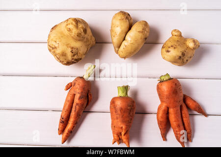 Flat lay Some ugly curved organic carrots and potatoes on white wooden background. - Stock Photo