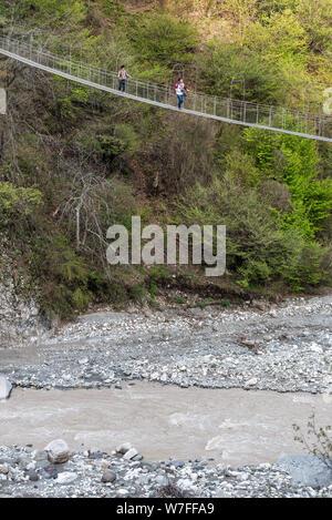 Lahic, Ismayilli region, Azerbaijan - April 27, 2019. Zarnava suspension footbridge bridge over Ghirdiman river near Lahic village, with people. - Stock Photo
