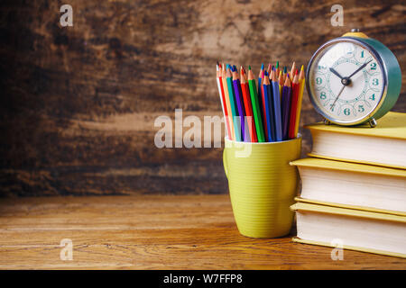 Colored pencils in a glass next to books and watche. Group of school supplies and books on wooden table. On a wooden background - Stock Photo