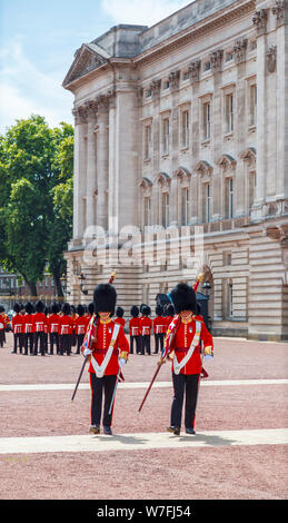 Soldiers in traditional red uniforms, members of the Queen's Guard, on parade at the changing of the guard ceremony at Buckingham Palace, London - Stock Photo