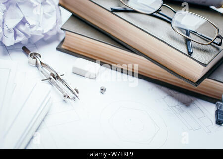 Books, glasses, pencil, compass and rolls of drawings on the details of industrial drawings. Engineering and technology. Technical drawing. - Stock Photo