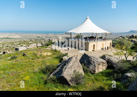 Gobustan, Azerbaijan - May 1, 2019. Landscape in Gobustan national park, with pavilion, people and Gobustan settlement in the distance. - Stock Photo